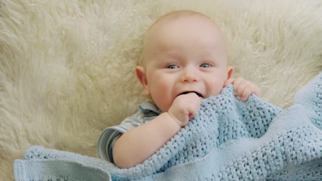 adorable baby looks at camera - soft blanket stock videos and b-roll footage