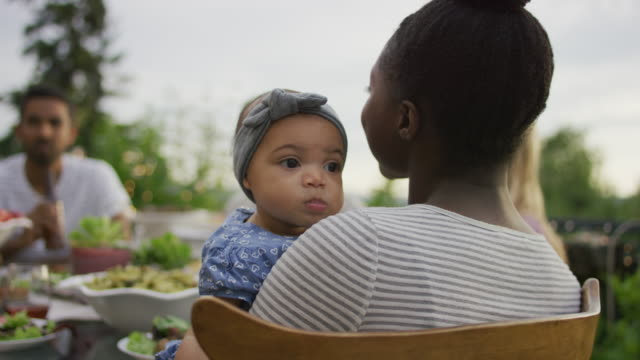 Adorable biracial baby looking over her mothers shoulder