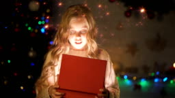 Adorable blond girl opening gift box, magic Christmas atmosphere, glowing effect