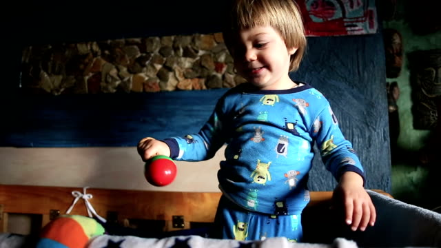 adorable blond kid playing with toy rattle - pyjamas stock videos and b-roll footage
