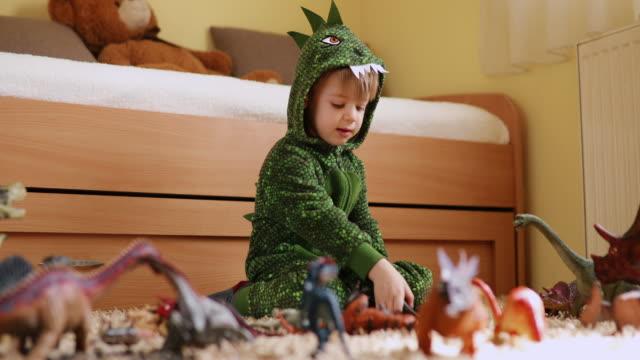 vídeos de stock, filmes e b-roll de menino adorável em uma fantasia de dinossauro brincando com seus dinossauros - jurássico