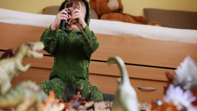 vídeos de stock, filmes e b-roll de menino adorável brincando com dinossauros - jurássico