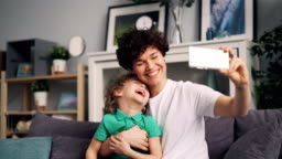 Adorable child and young lady mom taking selfie with smartphone camera laughing