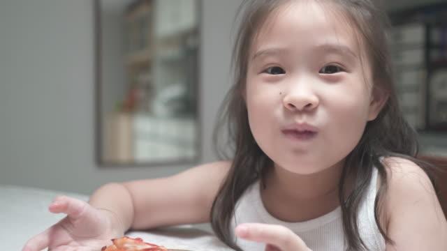 cu愛らしい女の子と彼女の母親は自宅でピザのスライスを食べることを楽しむ - unhealthy eating点の映像素材/bロール