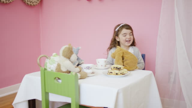 Adorable girl having a tea party with her stuffed animals