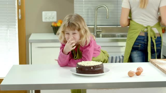 vídeos de stock, filmes e b-roll de hd dolly: adorável garota degustação um bolo - finishing touch