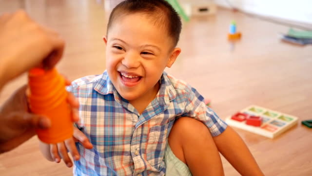 Adorable Hispanic boy with Down's Syndrome laughs as he teacher blows bubbles