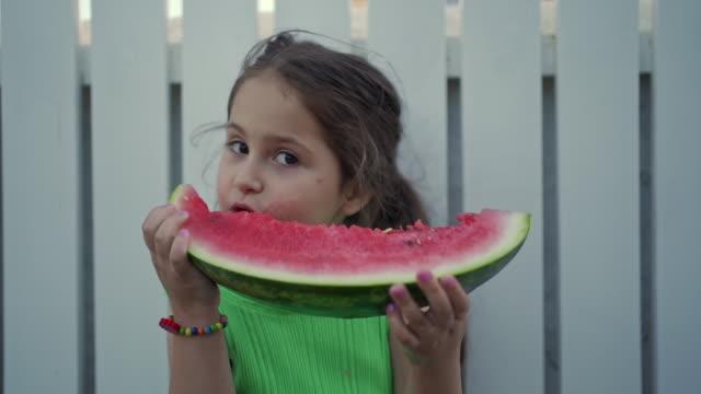 Adorável menina alegre desfrutando de melancia fresca suculenta