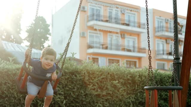 vídeos y material grabado en eventos de stock de adorable niño divirtiéndose en un columpio - columpio