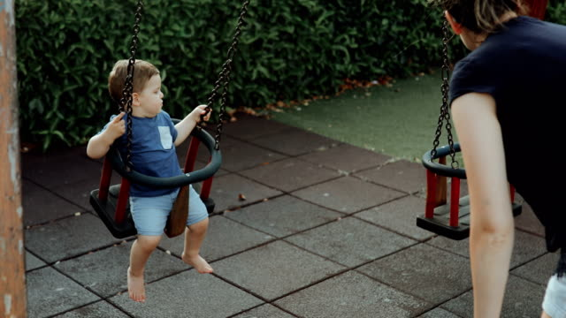 adorable little boy having fun on a swing with mom - swing stock videos & royalty-free footage