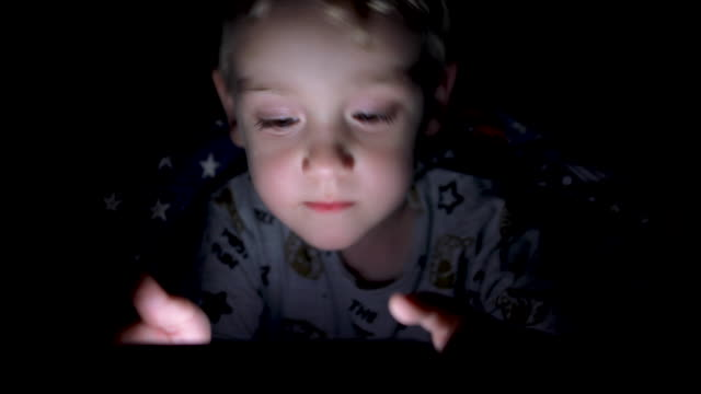 adorable little boy playing smartphone lying on a bed at night - star shape stock videos & royalty-free footage