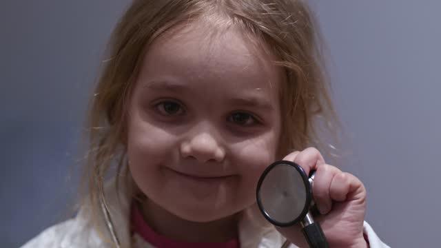 vídeos y material grabado en eventos de stock de adorable niña doctor sosteniendo un estetoscopio - 4 5 años