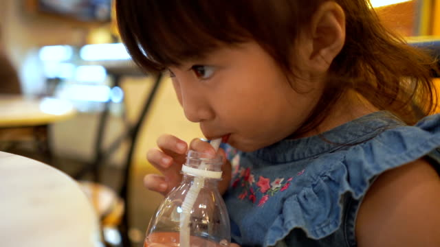 adorable little girl drinking water from plastic bottle , slow motion - straw stock videos & royalty-free footage
