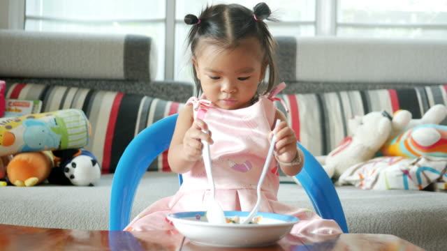vídeos y material grabado en eventos de stock de adorable niña comer alimentos - comida de bebé