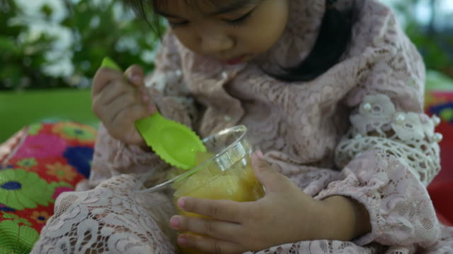 Adorable Little girl Eating Fruit