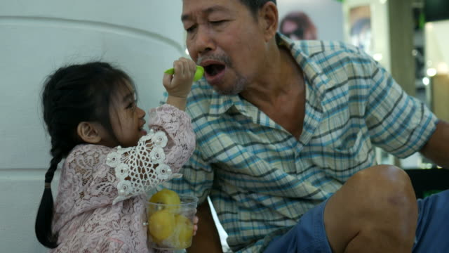 adorable little girl eating fruit with grandfather - spoon stock videos & royalty-free footage