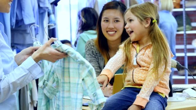 adorable little girl picks out shirt at clothing store - department store stock videos & royalty-free footage