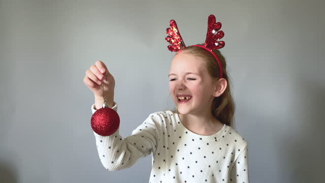 adorable little girl plays with christmas decorations against gray studio background - antler stock videos & royalty-free footage