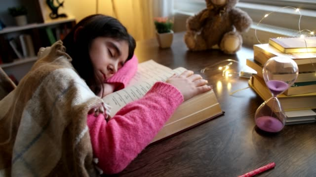 adorable little girl sleeping on a of books over - bedtime stock videos & royalty-free footage