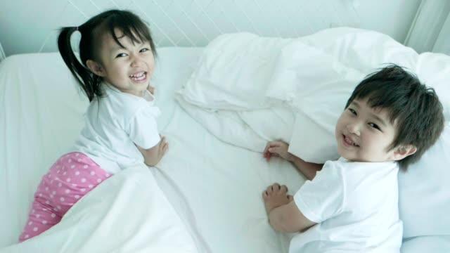アジアの兄と妹の愛らしいは、隠れていると肯定的な感情を持つカメラを見ながら横たわっています - 隠れる点の映像素材/bロール