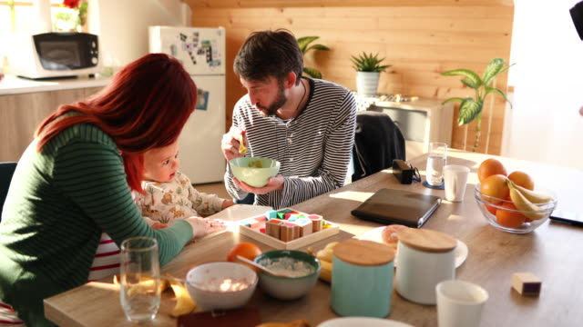 vídeos de stock e filmes b-roll de adorable parents trying to spoon fed their picky one year old boy - branco