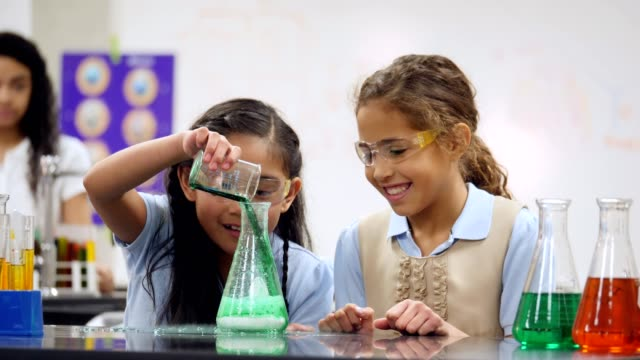 adorable private elementary stem school students conduct science experiment - becher video stock e b–roll
