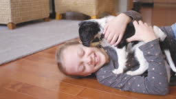 Adorable puppy licks young owner while she hugs him.