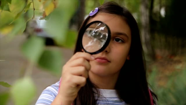 Adorable schoolgirl looking at a plant through a magnifying glass