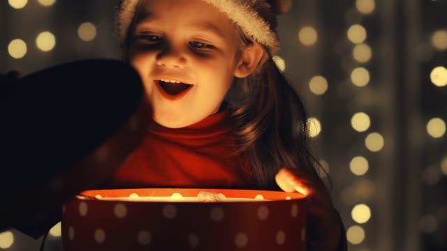愛らしい3歳の女の子は彼女のクリスマスプレゼントを開き、中にテディベアを見つける - 贈り物点の映像素材/bロール