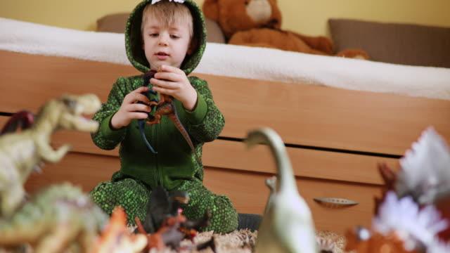 vídeos de stock, filmes e b-roll de adorável menino bebê em uma fantasia de dinossauro brincando com seus dinossauros - jurássico