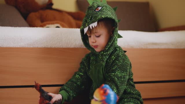 vídeos de stock, filmes e b-roll de adorável menino criança brincando com seus dinossauros - jurássico