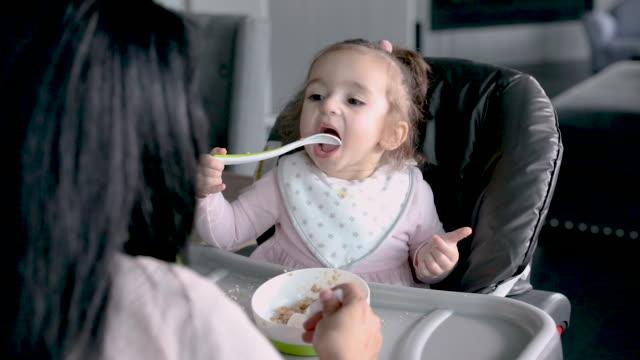 vidéos et rushes de la fille adorable d'enfant en bas âge mange la nourriture de chéri tout en s'asseyant dans la chaise élevée - céréale