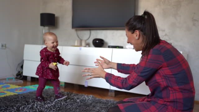 adorable toddler hardly keeping balance in her first steps to her mother - family with two children stock videos & royalty-free footage