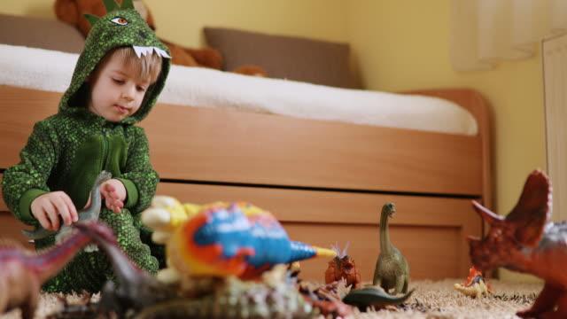 vídeos de stock, filmes e b-roll de criança adorável em uma fantasia de dinossauro brincando com seus dinossauros - jurássico