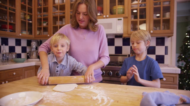 adorable young boy rolling cookie dough with rolling-pin - rolling pin stock videos & royalty-free footage