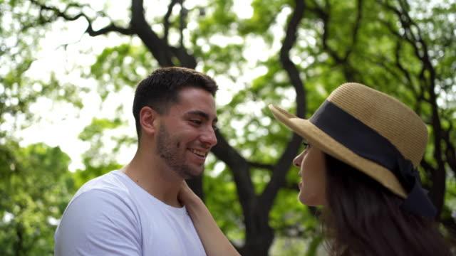 vidéos et rushes de jeune couples adorables flirtant sur leur date au stationnement public - coup de foudre