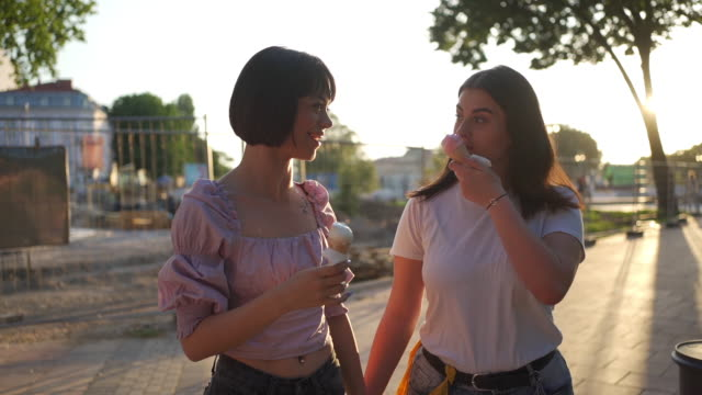 adorable young lesbian couple enjoying refreshing ice cream during summer walk - belly button piercing stock videos & royalty-free footage