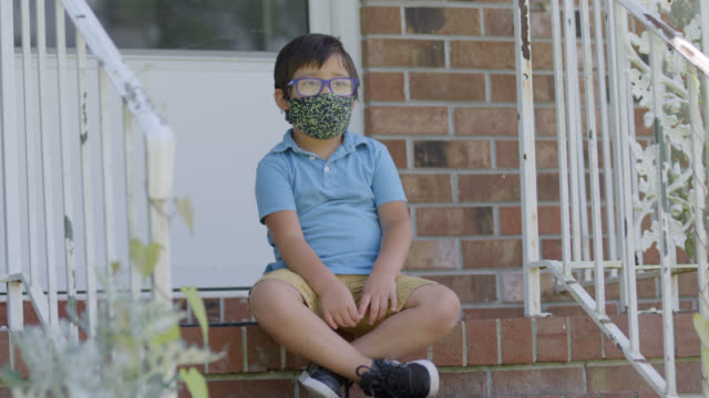 slo mo adorable young native-american boy wearing a protective face mask sits on his front porch - veranda stock videos & royalty-free footage
