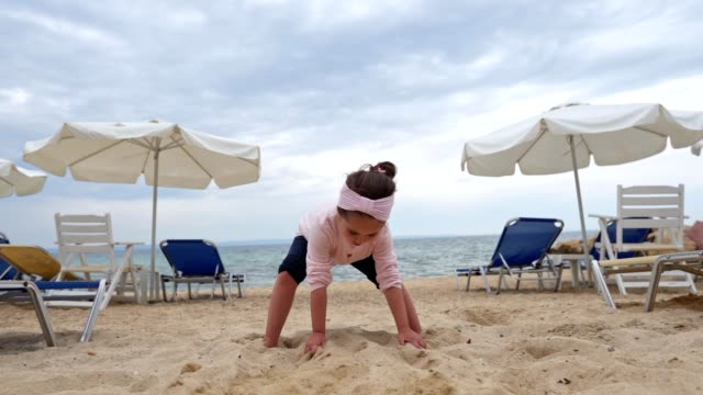 adorbale girl dancing on the beach and playing with a sand - chair stock videos & royalty-free footage