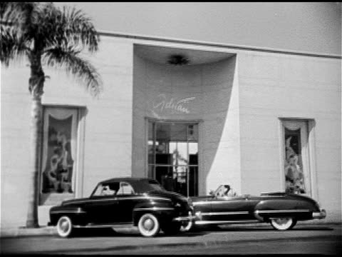 vidéos et rushes de ws 'adrian' designer clothing salon w/ convertibles parked on curb vs models modeling design gowns for clients in salon seated women watching model... - beverly hills