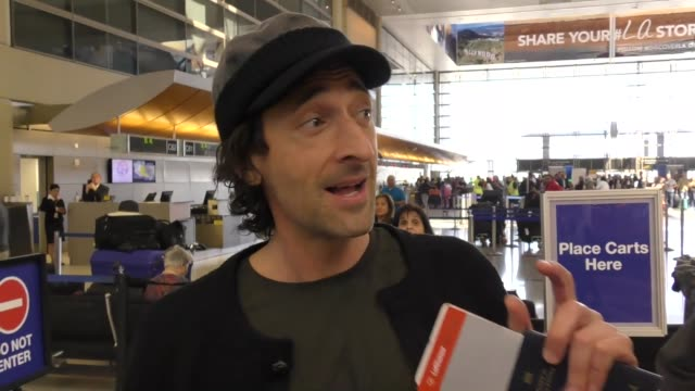INTERVIEW Adrien Brody talks about Donald Trump cutting off money to support the arts while departing at LAX Airport in Los Angeles in Celebrity...
