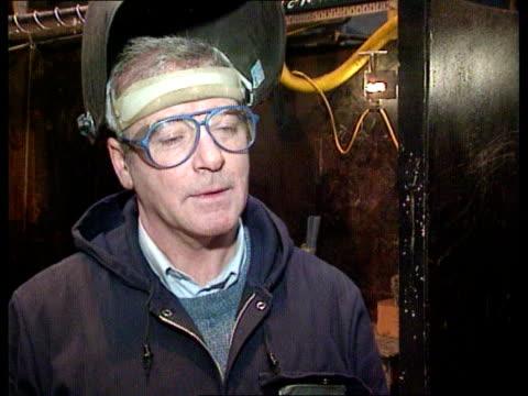 Adult apprentice scheme SCOTLAND Glasgow Govan Shipyards MS Welding apprentice as finishes welding and lifts facemask TILT UP CMS Welders being...