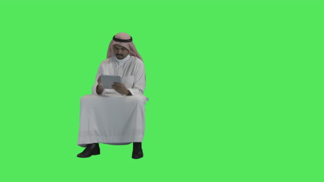 Adult Arabic Male sitting reading on digital tablet