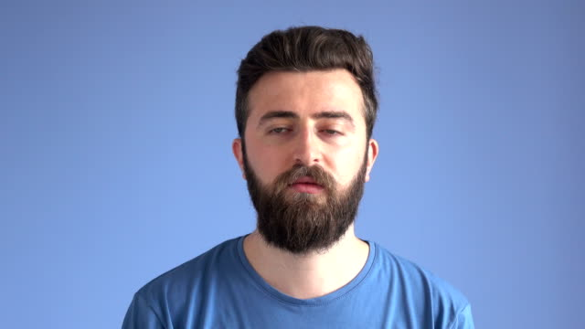 adult arrogant man making facial expression on blue background - attitude stock videos & royalty-free footage