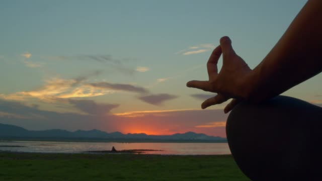 adult asian sport woman yoga ,meditating in lotus pose pose on the beach when sunset.4k dci footage.light leaking of sun flare.silhouette shot. - lotus position stock videos & royalty-free footage