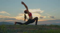 Adult asian sport woman yoga pose on the beach when sunset.4k dci footage.Silhouette shot.