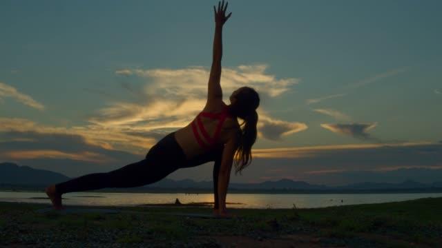 vídeos de stock, filmes e b-roll de a mulher asiática asiática asiática ioga pose na praia quando sunset.4k dci footage. tiro de silhueta. - braço humano