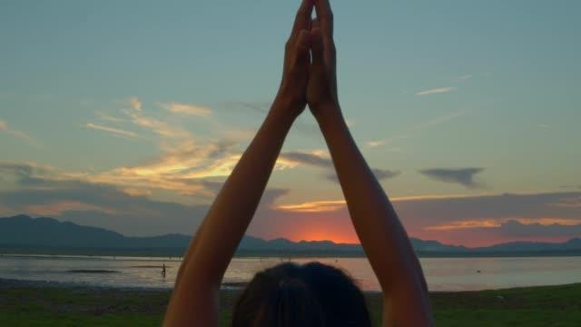 vídeos de stock, filmes e b-roll de a mulher asiática asiática asiática ioga pose na praia quando sunset.4k dci footage. - braço humano