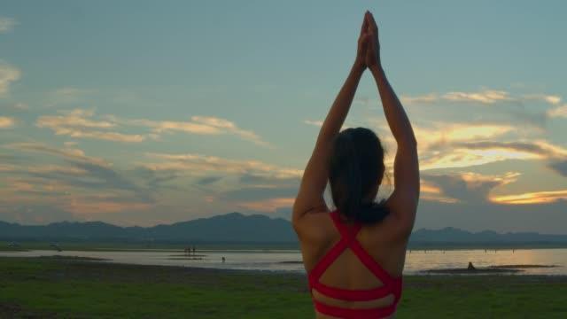 vidéos et rushes de adulte asiatique sport femme yoga pose sur la plage lorsque sunset.4k dci images. - membres du corps humain