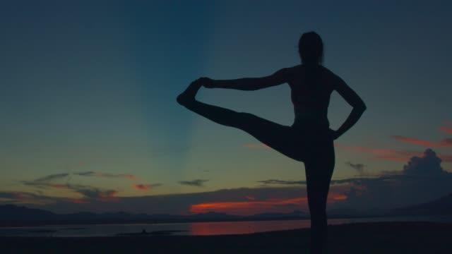 vidéos et rushes de adulte asiatique sport femme yoga pose sur la plage lorsque sunset.4k dci images. silhouette prise. - membres du corps humain